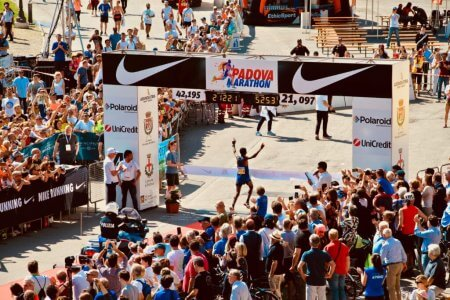 Image of runner crossing finish line cheered on by crowds