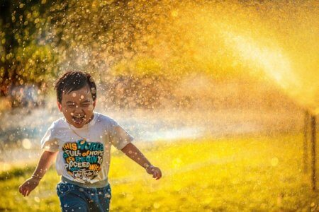 Image of a little boy running through sprinklers, laughing, on a sunny day. Photo by Mi Pham via Unsplash.