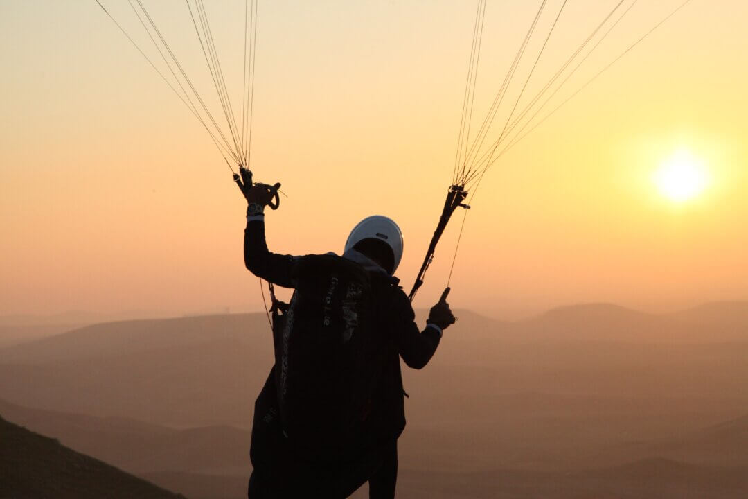 Image of someone in a harness attached to a parachute, with a view of mountains and the sun setting.