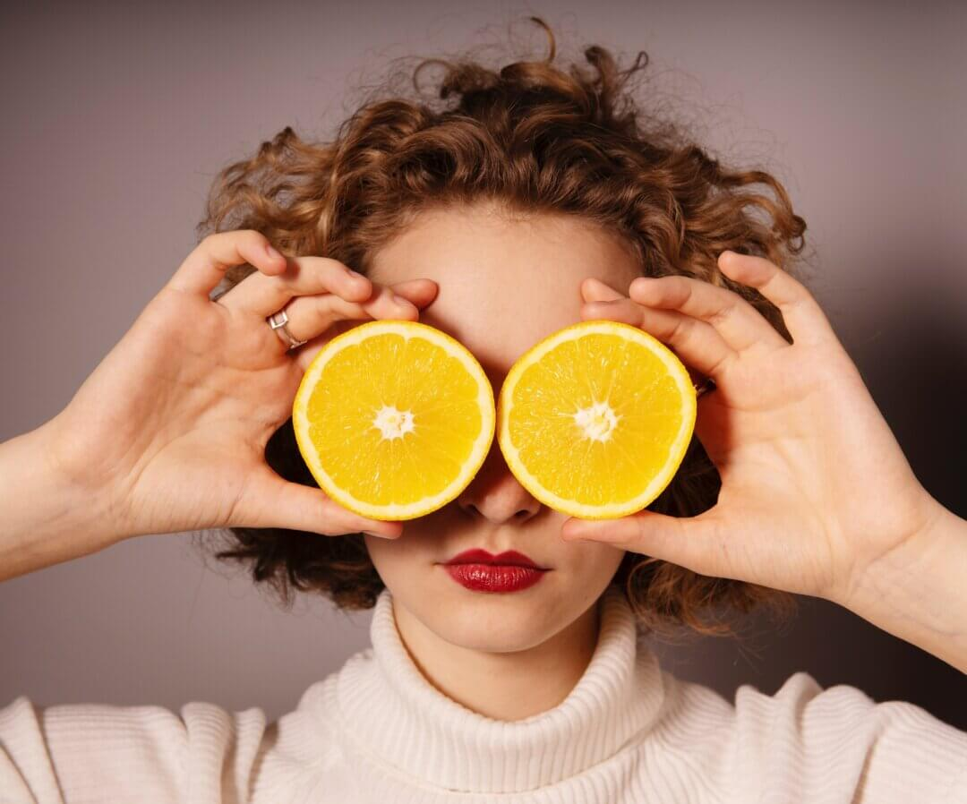 A woman holds two orange halves in front of her eyes. With eating disorders like orthorexia there can be an obsession with clean eating. We need to be aware of red flags for disordered eating in therapy.