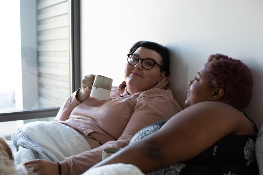 Two plus size people in bed looking at each other and drinking coffee. Therapists need to understand gender, sexual and relationship diversity to ensure clients have a good and non-harmful experience in counselling.