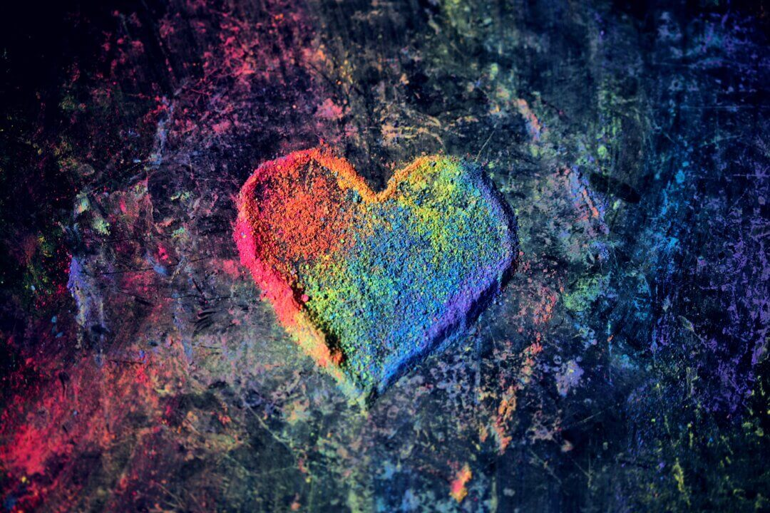 Image of a heart made out of coloured sand in varying colours, against a black background with paint splashes. Gender, sexual and relationship diversity is something all therapists should understand.