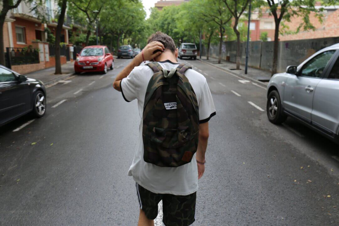 Image of an adolescent boy on a road, from behind, wearing a backpack with his hand on his head. Therapy can help young people offload emotional problems.